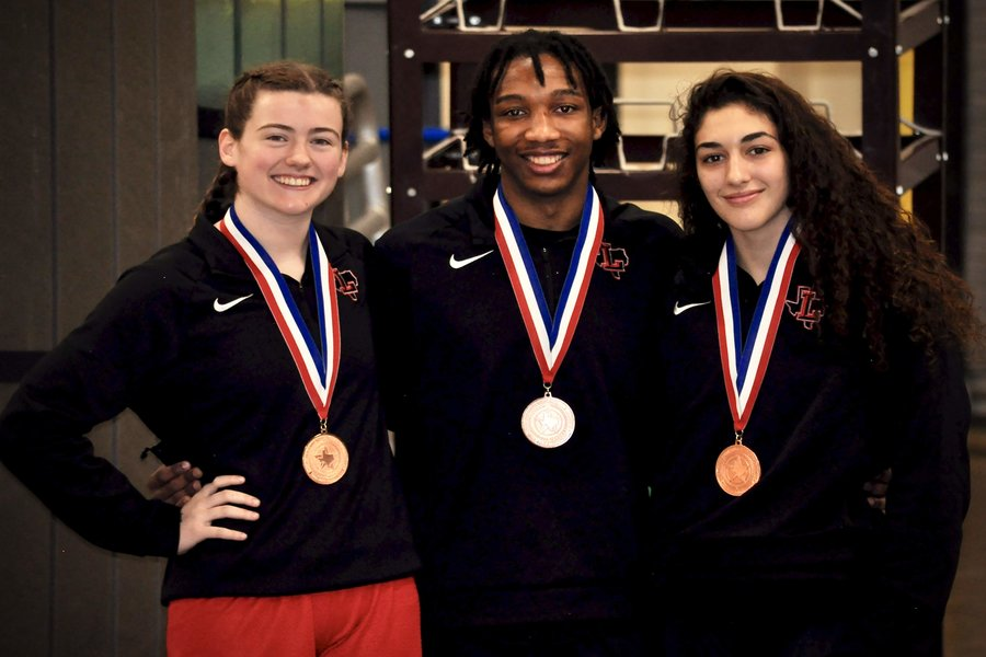 Posing with their medals, seniors Daley Burkett, Tristan Seales, and Emily Corona celebrate the end of the wrestling season at the state tournament at Cypress Fairbanks area. After months of regular season, and three weeks of UIL finals matches, Redhawk wrestling returns with six athletes taking top six in Texas for their weight class.