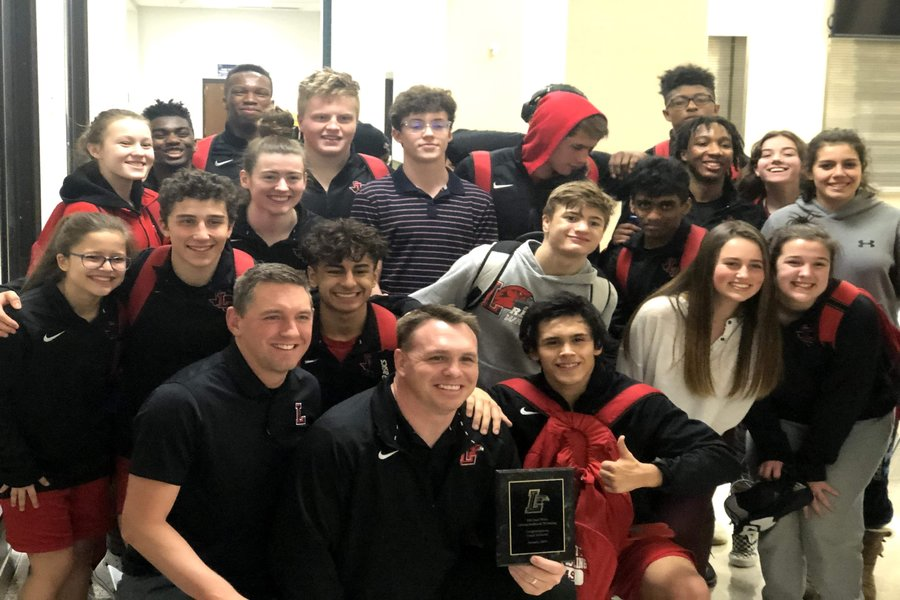Celebrating coach Cody Bridwells 100th win, the team poses for a picture with Bridwells new plaque. The teams dual season is over, but the team is now looking forward to bigger things to come at the district tournament Friday Feb. 7.