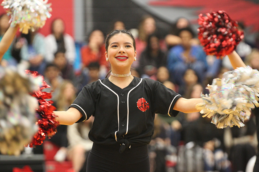 Sophomore Sophia Reeves smiles for the audience during Red Rhythm's pom routine at the spring pep rally on Tuesday, Feb. 11, 2020.