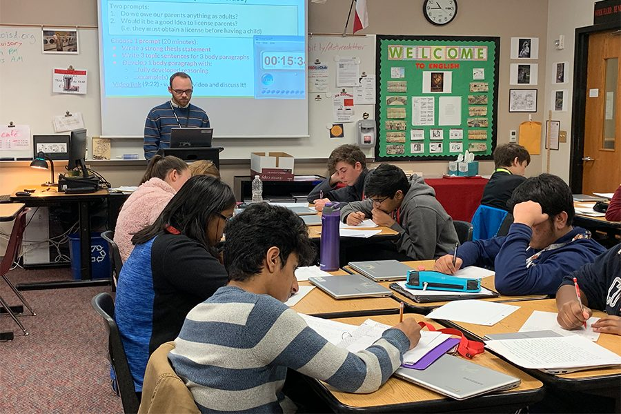 Delivering a lecture to his students, AP Seminar teacher Chad Doty is concerned about how a merit-based pay system would be implemented.