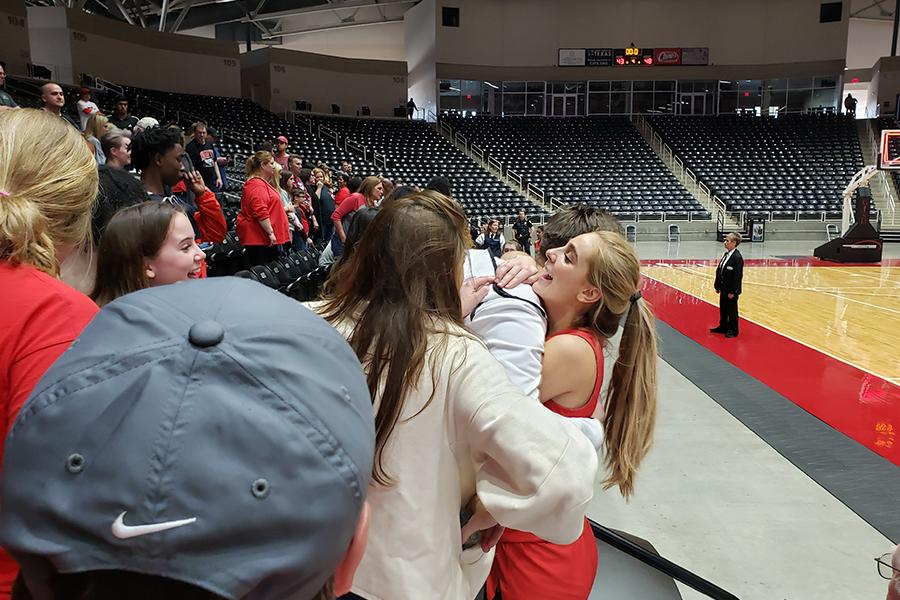 Hitting a 3-point shot in the third OT that gave the Redhawks a four point lead they wouldn't relinquish, junior Lily Ziemkiewicz hugs family and friends at the end of the 5A Region II final in Garland. The Redhawks advanced to the state semifinals after beating Midlothian 48-43 on Saturday, Feb. 29, 2020.