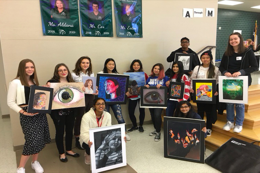 Art teacher Jeb Matulich's class poses with their art work at Reedy High School. Sophomore Sarah Boutouis (second from the left) was the only student from all three art teachers on campus to advance to the state level.
