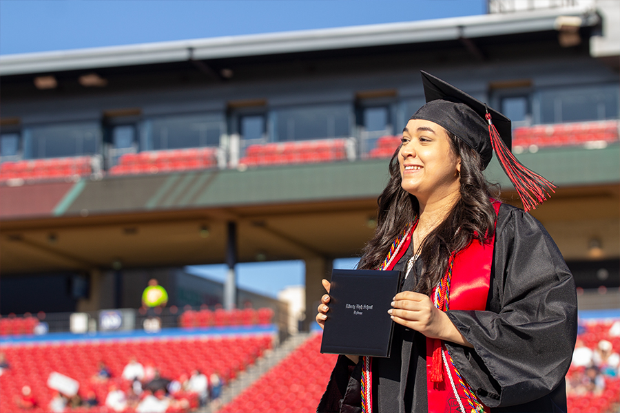 Posing for a picture, senior Kanz Bitar holds her diploma on the stage at Toyota Stadium for the class of 2020 graduation on Saturday, May 30, 2020.