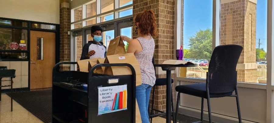 Archit Gnalke picks up books from the book takeout program, which allows students to check out books from the library during virtual learning.