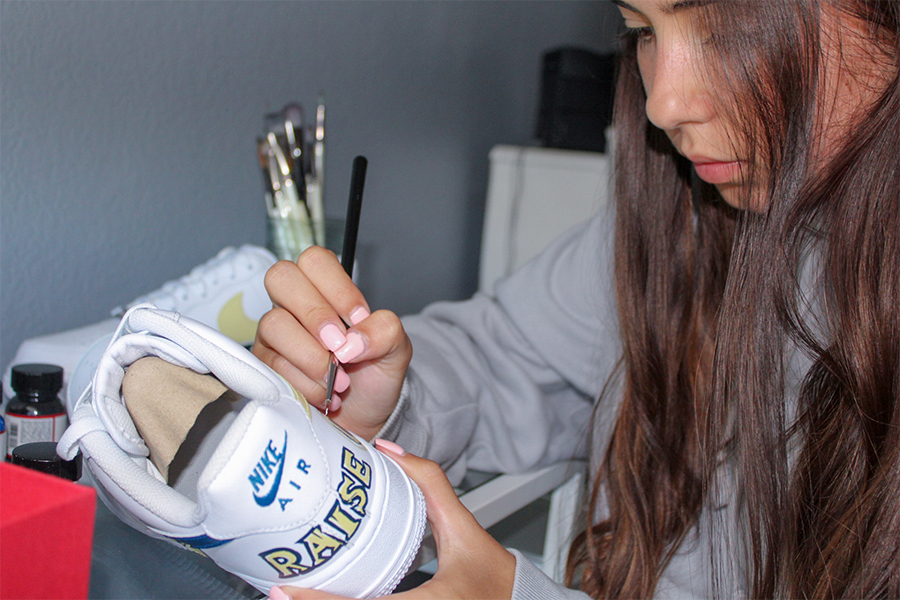 """Senior Emily Chladny paints on a pair of Nike shoes. Chladny has learned that the most important task of customizing a shoe is creating something that is coherent.  """"Now having customers I am having to take in their ideas and factor them into what I believe would make the best coherent shoe design,"""" she said."""