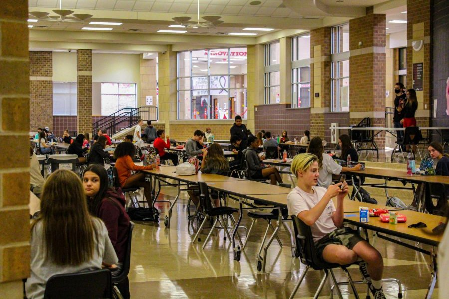 Students+eat+their+lunches+while+social+distancing+in+the+cafeteria.+With+more+students+returning+to+campus+after+having+the+opportunity+to+switch+learning+environments.+%E2%80%9CWhen+looking+at+the+impact+%5Bof+more+students+returning+to+campus%5D%2C+we+have+to+look+at+the+safety+and+security+of+our+campus+in+general%2C%E2%80%9D+principal+Ashley+Rainwater+said.+%E2%80%9CWe%E2%80%99re+going+to+look+at+numbers+in+our+lunchroom%2C+look+at+numbers+in+bathrooms%2C+look+at+our+numbers+in+our+hallways+to+make+sure+we%E2%80%99re+able+to+socially+distance+while+we%E2%80%99re+at+school.%E2%80%9D+%0A