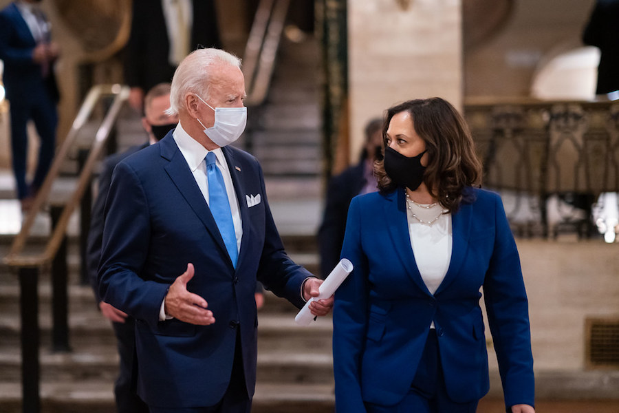 Wearing masks, President-elect Joe Biden talks with Vice President-elect Kamala Harris. A focus for the Biden Administration will be working to combat COVID-19, of which Biden plans to do so through various ways to restore people's trust in the government during a crisis, including centering scientists and public health officials, making testing widely affordable and available, as well as reinstating the National Security Council Directorate for Global Health Security and Biodefense Dissolved, to name a few.