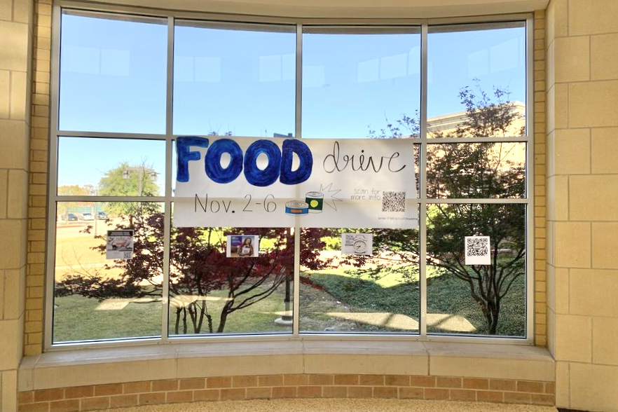 A poster promoting StuCos annual Nov. food drive hangs in the rotunda. A QR code hangs to the right of the poster, which has Amazon links to the items that can be donated as the event is online this year.