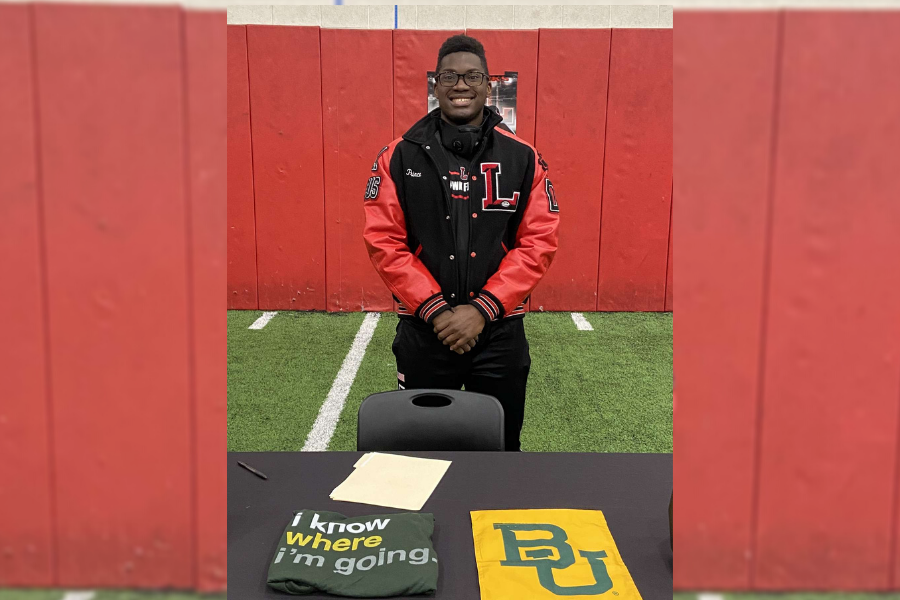 Posing in front of a table of Baylor University gear, Prince Ugoh signed his letter of intent to continue playing football beginning in the fall.