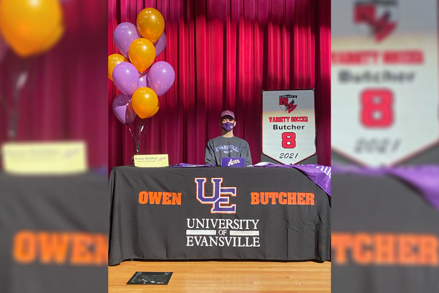 Owen Butcher poses at a table decorated in the University of Evansville gear, where he will continue his soccer career starting in the fall.