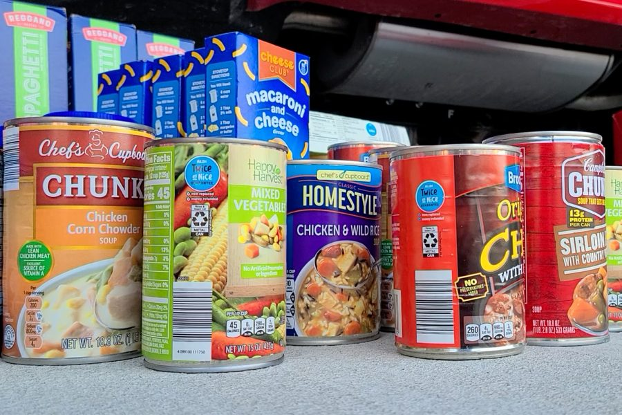 Canned food and other non-perishable food items are among the items journalism adviser Brian Higgins and his 12-year-old son Owen bought on Saturday for Monday's food and water drive sponsored by PALs, Student Council, and Wingspan.
