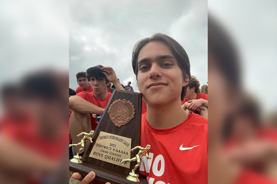 Posing with the boys cross country team regional qualifier trophy, junior Andrew Jáuregui and the Redhawks finished 3rd in the District 9-5A meet at Warren Park on Oct. 15, 2021.